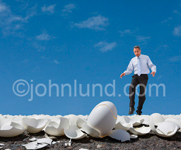 Conceptual picture of a man walking on egg shells.  Business man is wearing a dress shirt and tie and is walking on tip toe.
